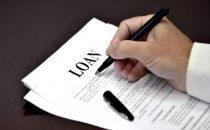 אדם חותם על טופס של הלוואה חוץ בנקאית