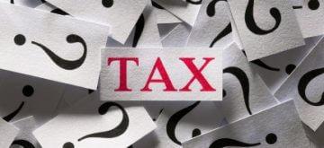 פתק של המילה מס וסימני שאלה לידיו