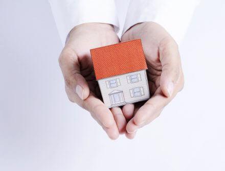 דגם של בית בכפות הידיים