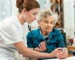 אישה מבוגרת עם האחות שהוקצתה לה במסגרת ביטוח זיקנה
