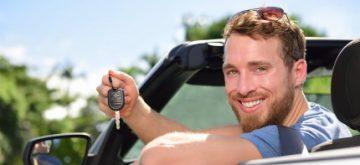 אדם שמח ברכב חדש שרכש בעסקת ליסינג