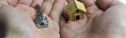 בית ומפתח בתוך כפות ידיים