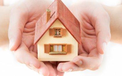 ידיים מחזיקות דגם מוקטן של בית