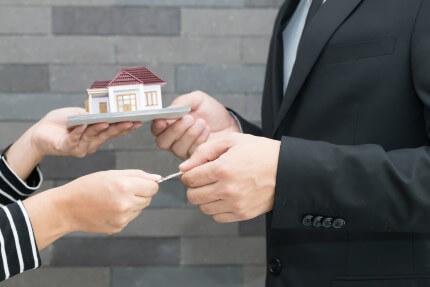 בנקאי מגיש לאישה דגם של בית תמורת כסף