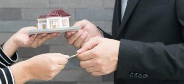אשה מגישה דגם של בית תמורת כסף