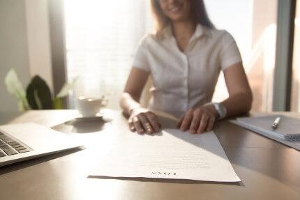 אישה חותמת על טפסים לקבלת הלוואה