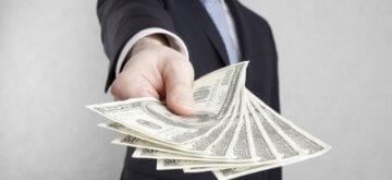 איש עסקים מושיט שטרות דולרים להלוואה
