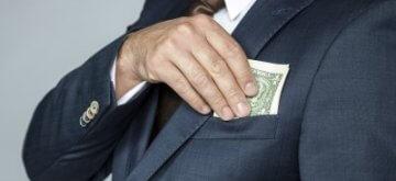 איש עסקים מחזיק כסף שניתן לו כהלוואה מקרן דטרויט