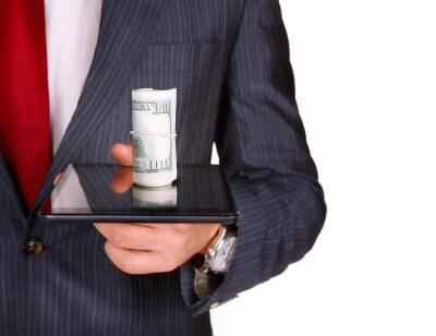 אדם מחזיק כסף על טאבלט