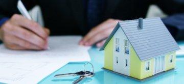 דגם של בית ומפתחות על רקע אדם חותם על טופס להשתתפות במחיר למשתכן