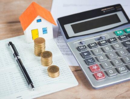 מחשבון לצד דגם של בית במחיר למשתכן ומטבעות