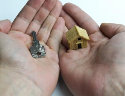 כפות ידיים של אדם אוחזות במפתח ובדגם מיניאטורי של בית