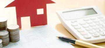 דגם של בית לצד מחשבון, מסמכים ועט