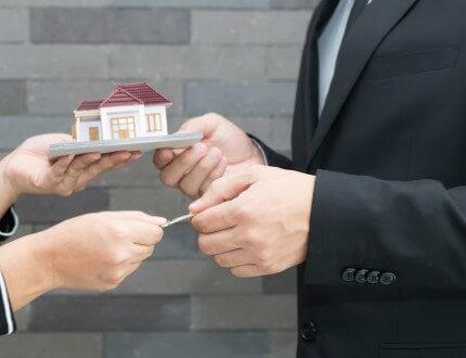 אדם מחזיק מפתח ודגם של בית