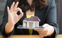 אישה מחזיקה בדגם קטן של בית