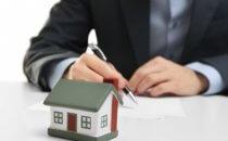 דגם קטן של בית ועט מונחים על שולחן
