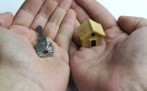 כפות ידיים אוחזות בדגם קטן של בית