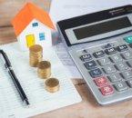 דגם של בית לצד מחשבון ומטבעות