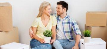 זוג צעיר יושב עם קרטונים בדירה החדשה
