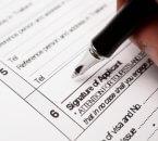 אדם חותם על טופס הלוואה לחברת אבטחה בערבות המדינה